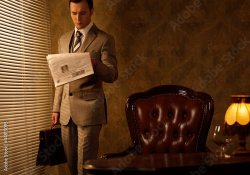 Retro businessman reading newspaper