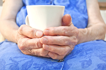 Senior hand hold a cup of tea