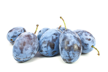 Fresh blue plums on the white background