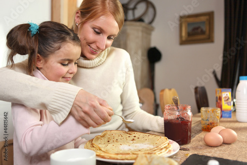 loving mother making crepes with little girl