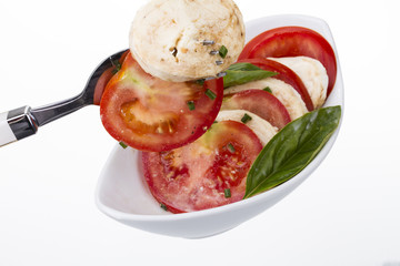 tomaten mit mozzarella mit basilikum auf gabel