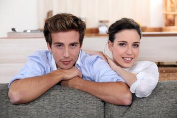 Couple behind sofa