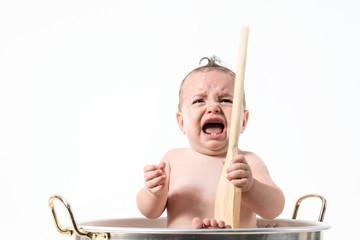 Bambina che piange dentro la pentola con il mestolo