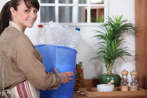 Woman with plastic bottle for recycling