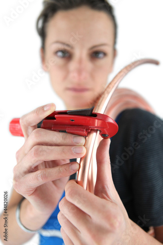 Female plumber cutting copper pipe with special tool