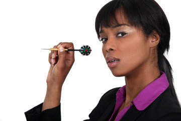 Businesswoman throwing a dart