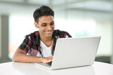 Young Indian man using a laptop