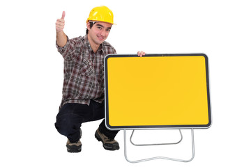Worker kneeling by blank road sign