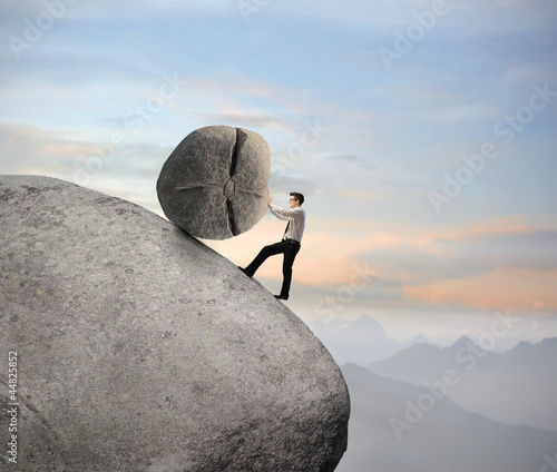 Businessman pushing a boulder on a rock