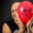 Happy man hiding behind angry balloon