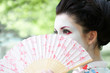Portrait of young woman with geisha style makeup and fan