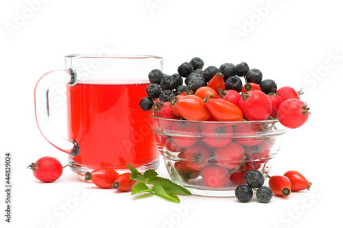 cup of tea with rose hips and different berries close up