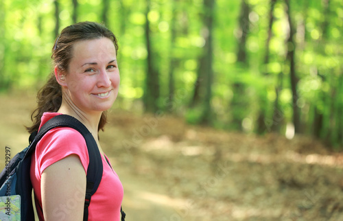 Smiling woman hiking in forest