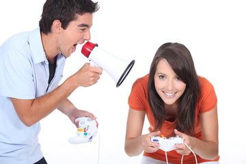 Man shouting into megaphone as girlfriend plays video game