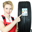 Female car mechanic showcases tire label
