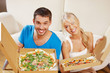 romantic couple eating pizza at home