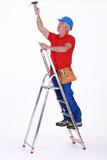 Tradesman installing a light fixture poster