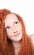 Freckled red haired girl looking up