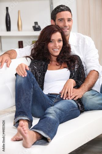 Young couple sat on couch at home