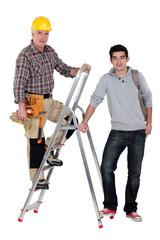 Builder stood on ladder next to apprentice