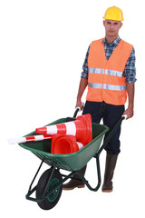 Roadworker with cones in a wheelbarrow
