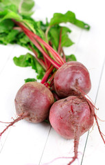Three red beets with leaves