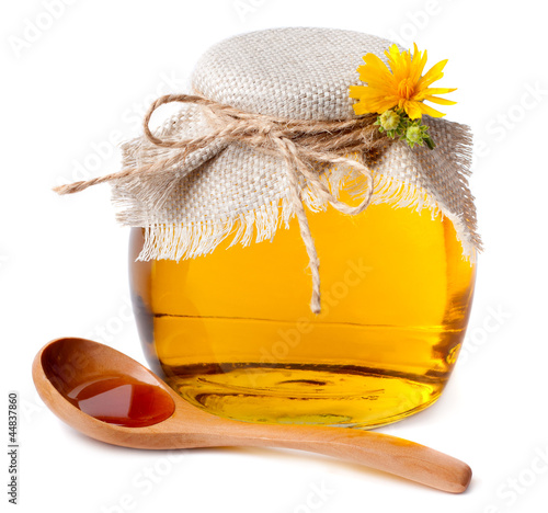 Honey in the pot and a wooden spoon