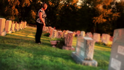 Woman Visits Grave in Cemetery