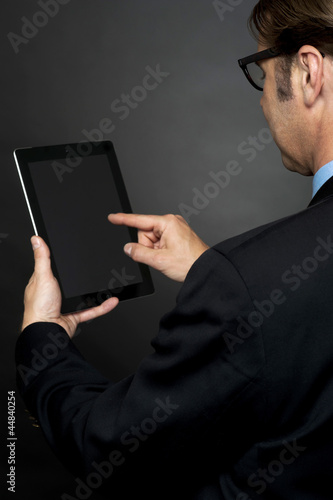 Rear view of boss browsing on new tablet pc