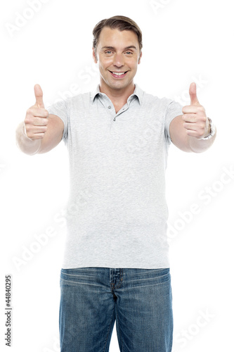Good looking cheerful man showing double thumbs up