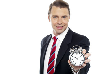 Smiling young consultant showing alarm clock