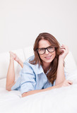 Attractive woman wearing glasses in bed