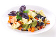 Pasta farfalle with vegetables on white plate.