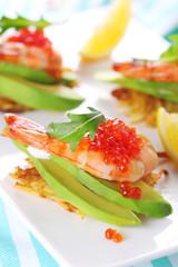 Appetizer with shrimp, avocado and caviar on potato pancakes