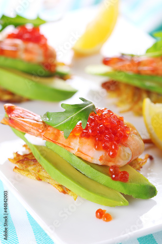 Appetizer with shrimp, avocado and caviar on potato pancakes