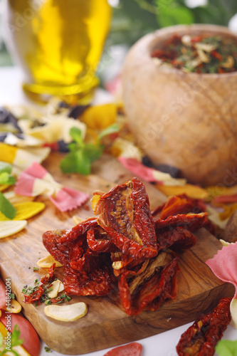 Dried tomatoes, garlic, basil, ingredients of Italian cuisine.