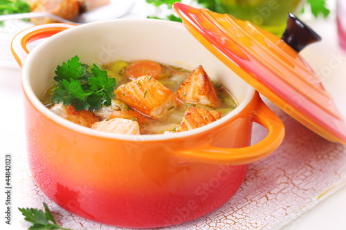 Soup with vegetables and salmon in ceramic pot.