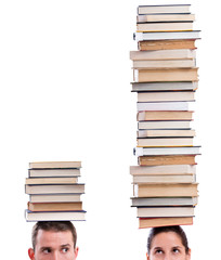 Man and woman holding books on their heads