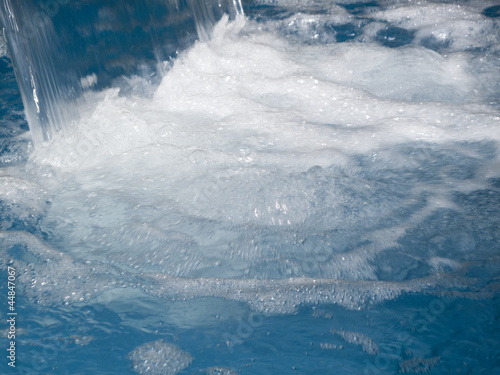Close up of water splashing into swimming pool