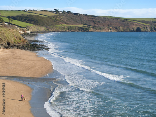 Woman and dog enjoying beach and ocean at Gerrans Bay, Cornwall, United Kingdom