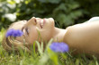 Close-up portrait of young woman lying in grass with flowers