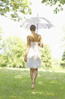 Rear view of young woman walking in grass holding an umbrella