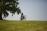 Young businessman riding bicycle in grass and holding chair
