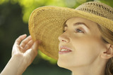 Close-up portrait of young woman in straw hat outdoors
