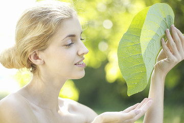Portrait of young woman holding big leaf outdoors