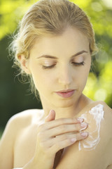 Portrait of young woman putting lotion on shoulder outdoors