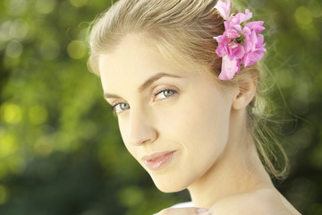 Portrait of young woman with pink flower in hair outdoors