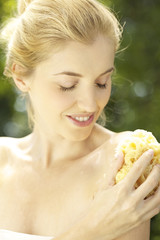 Portrait of young woman bathing with sponge outdoors