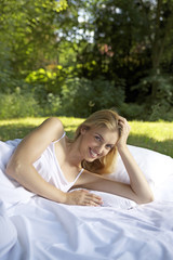 Portrait of young woman lying outdoors in sheets