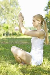 Portrait of young woman practicing yoga in grass